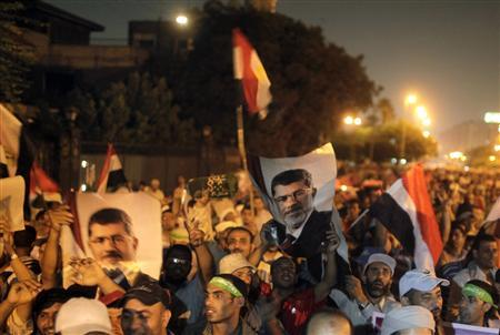 Supporters of deposed Egyptian president Mohamed Mursi hold up Egyptian national flags and posters of Mursi, as they chant slogans during a rally on a main street in Cairo July 19, 2013. REUTERS/Asmaa Waguih