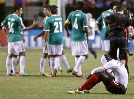 Trinidad & Tobago's Sean Power (R), reacts at the end of the game as Mexico teammates celebrate during their CONCACAF Gold Cup soccer game in Atlanta, Georgia July 20, 2013. REUTERS/Tami Chappell