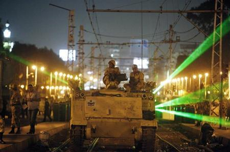 Egyptian Army soldiers sit on an armoured personnel carrier (APC) on a tram track, during a patrol, as supporters of deposed president Mohamed Mursi approach the presidential palace in Cairo, July 19, 2013. REUTERS/Asmaa Waguih