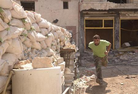 A Syrian army soldier loyal to Syria's President Bashar Al-Assad runs past sandbags to take cover in Aleppo's Karm al-Jabal district July 18, 2013. REUTERS/George Ourfalian