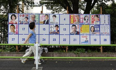 A woman with a dog walks past a poster of election candidates for the upper house election near a polling station in Tokyo July 21, 2013. REUTERS/Yuya Shino