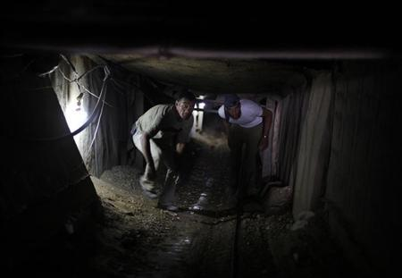 Palestinian tunnel workers walk inside a smuggling tunnel dug beneath the Gaza-Egypt border in the southern Gaza Strip July 19, 2013. REUTERS/Ibraheem Abu Mustafa