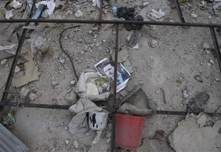 A picture of Syria's President Bashar al-Assad is seen among rubble in Aleppo's Karm al-Jabal neighbourhood, July 21, 2013. REUTERS/Muzaffar Salman