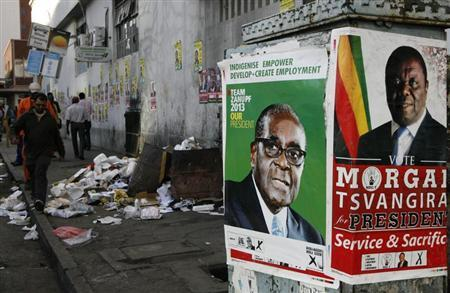 Election campaign posters are pictured near Zimbabweans walking on a street blocked by uncollected garbage in Harare July 17, 2013. REUTERS/Philimon Bulawayo