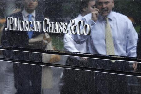 Commuters are reflected in stone as they walk past the JP Morgan headquarters in New York May 22, 2012.REUTERS/Eduardo Munoz