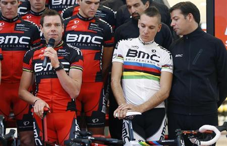 BMC Racing Team rider Cadel Evans (L) of Australia speaks next to rider Philippe Gilbert of Belgium and sports director John Lelangue (R) during the cycling team's official presentation in Nazareth, near Ghent January 11, 2013. REUTERS/Francois Lenoir