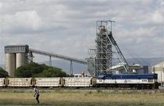 Мужчина проходит мимо грузового состава у шахты Anglo American Platinum в Рюстенбурге 15 января 2013 года. Южноафриканская Anglo American Platinum, крупнейший в мире производитель платины, почти удвоил прибыль в первом полугодии благодаря ослаблению местной валюты и увеличению продаж, сообщила компания в понедельник. REUTERS/Siphiwe Sibeko
