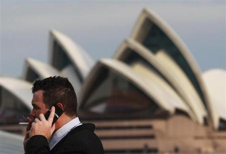 An office worker smokes a cigarette in front of the Sydney Opera House August 15, 2012. REUTERS/Daniel Munoz