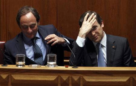 Portugal's Prime Minister Pedro Passos Coelho (R) adjusts his hair beside Foreign Minister Paulo Portas during a no-confidence session at the parliament in Lisbon July 18, 2013. REUTERS/Hugo Correia