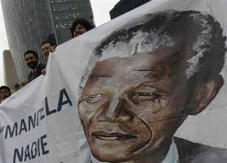 Well-wishers hold a giant banner with an image of former South African President Nelson Mandela during a celebration to mark Mandela's 95th birthday at the Angel de la Independencia monument in Mexico City July 18, 2013. REUTERS/Henry Romero