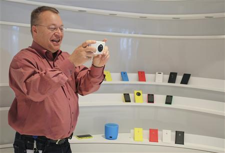 Nokia Chief Executive Stephen Elop demonstrates the camera technology of the company's latest high-end smartphone, the Lumia 1020, at the company's headquarters in Espoo, during an interview with Reuters, July 17, 2013. Picture taken July 17, 2013. REUTERS/Ritsuko Ando