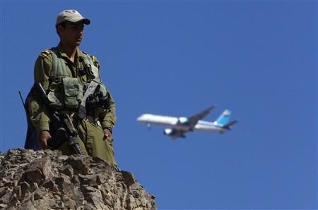 A plane flies overhead as an Israeli soldier stands guard near the Israeli-Egyptian border, close to the Red Sea resort of Eilat, in this August 19, 2011 file picture. REUTERS/Ronen Zvulun/Files