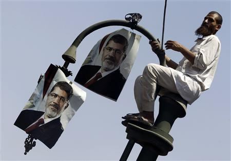A member of the Muslim Brotherhood and supporter of ousted Egyptian President Mohamed Mursi places posters of Mursi on a lamp post during a protest in front of the courthouse and the Attorney General's office in Cairo July 22, 2013. REUTERS/Amr Abdallah Dalsh