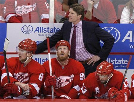 Detroit Red Wings head coach Mike Babcock stands behind Justin Abdelkader (8), Johan Franzen (seated C) and Pavel Datsyuk (seated R) in the final minutes of the third period against the Chicago Blackhawks during Game 6 of their NHL Western Conference semi-final hockey playoff game in Detroit, Michigan May 27, 2013. REUTERS/Rebecca Cook