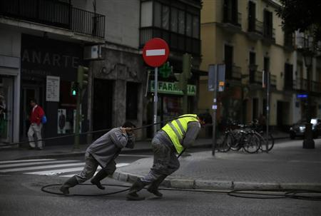 Workers pull optical fiber cable in the Andalusian capital of Seville, southern Spain April 9, 2013. REUTERS/Marcelo del Pozo