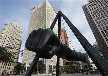 A sculptor of a giant fist in honor of American boxer and heavy weight champion Joe Louis sits at the intersection of Woodward and Jefferson Avenue in downtown Detroit, Michigan July 21, 2013. REUTERS/ Rebecca Cook