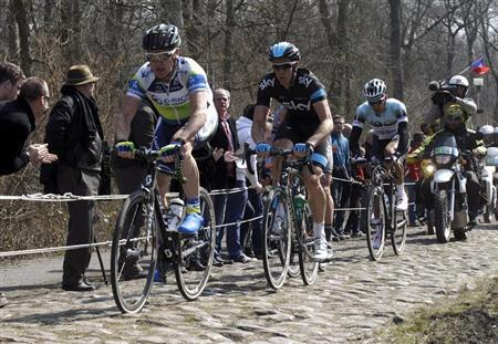 (L to R) Stuart O'Grady of Australia leads the breakaway followed by Mathew Hayman of Australia and Gert Steegmans of Belgium as they cycle on the Arenberg cobble-stoned section during the Paris-Roubaix cycling race from Compiegne to Roubaix, April 7, 2013. REUTERS/Pascal Rossignol