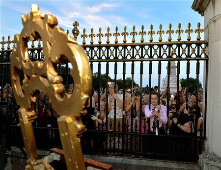 Crowds of people try to look at a notice formally announcing the birth of a son to Prince William and Catherine, Duchess of Cambridge, placed in the forecourt of Buckingham Palace, in central London July 22, 2013. REUTERS/John Stillwell/Pool