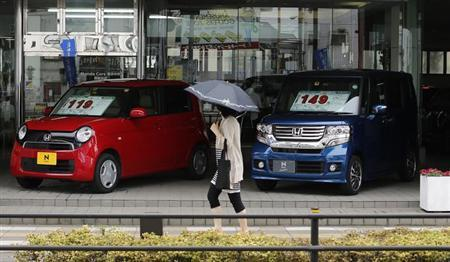 A woman walks past Honda Motor Co's N Box (R) and N One minicars outside at a Honda dealer in Tokyo July 13, 2013. REUTERS/Toru Hanai