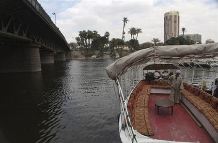 A man stands in his cruise boat as he waits for customers on the river Nile in Cairo April 22, 2013. REUTERS/Asmaa Waguih/Files