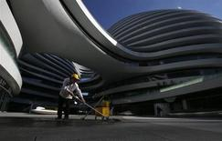 A cleaner works at a newly built business building in Beijing July 16, 2013. REUTERS/Kim Kyung-Hoon