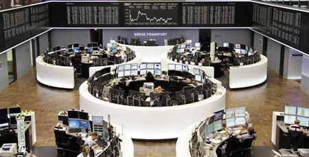 Traders work at their screens in front of the German share price index DAX board at the Frankfurt stock exchange July 22, 2013. REUTERS/Remote/Stringer