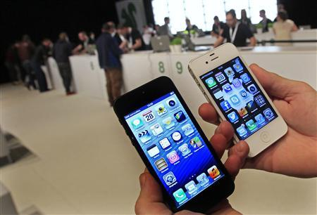 A customer holds up an Apple iPhone 5 (L) and iPhone 4S in Brussels in this September 28, 2012 file photo. REUTERS/Yves Herman/Files