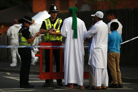Residents speak to police officers guarding a cordon after an explosion in Tipton, central England July 12, 2013. REUTERS/Darren Staples