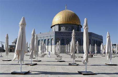 Palestinians walk amongst parasols placed outside the Dome of the Rock on the compound know to Muslims as ''al-Haram al-Sharif'' and to Jews as ''Temple Mount'' in Jerusalem's Old City June 27, 2013. REUTERS/Baz Ratner