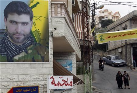 A poster of Mohamed Hassan Shehade, a Hezbollah fighter who died in the Syrian conflict, hangs on a building in Adloun town, south of Sidon in southern Lebanon, July 23, 2013. REUTERS/Ali Hashisho