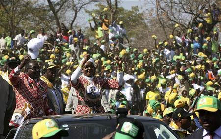 Zimbabwe President Robert Mugabe (L) and his wife Grace wave during an election rally in Chinhoyi, 115 km (70 miles) northwest of Harare, July 18, 2013. REUTERS/Philimon Bulawayo
