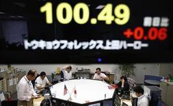 Un monitor electrónico presenta la cotización del yen japonés frente al dólar, mientras abajo puede verse un grupo de operadores en la bolsa de Tokio. Julio 22. 2013. El Gobierno de Japón mejoró su panorama sobre la economía por tercer mes consecutivo en julio y dijo que la deflación está cediendo como resultado de la mezcla de políticas monetarias expansivas del país y un generoso gasto. REUTERS/Yuya Shino