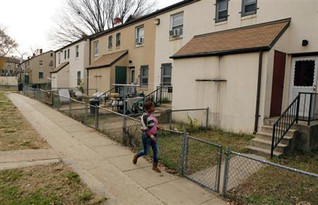 A woman walks on a path in the Berry Farm housing project in Ward 8 of Washington November 20, 2012. REUTERS/Kevin Lamarque