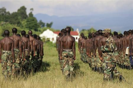 A M23 rebel trainer walks behind recruits during a training session at the Rumangabo military camp in eastern Democratic Republic of Congo, May 16, 2013. REUTERS/James Akena
