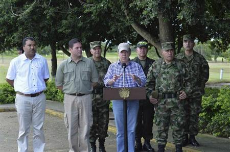 Colombia's President Juan Manuel Santos (C) speaks with Defense minister Juan Carlos Pinzon (2nd L) and the Army chief commander Gen. Alejandro Navas (2nd R) to the media at an army base in Tame, Arauca province in this July 21, 2013 picture provided by the Colombian Presidency. REUTERS/Juan Pablo Bello/Colombian Presidency/Handout via Reuters
