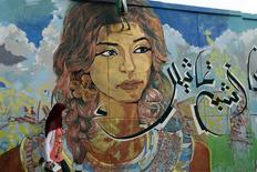 A girl walks past graffiti on a wall near Tahrir square in Cairo July 21, 2013. REUTERS/Asmaa Waguih