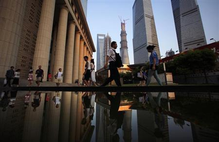 People walk to a subway station at the financial district of Pudong in Shanghai July 23, 2013. REUTERS/Carlos Barria