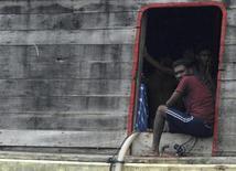 Мигранты из Шри-Ланки на грузовом судне в бухте города индонезийского города Чилегон 12 октября 2009 года. Судно, на борту которого находились около 170 человек, затонуло у берегов Индонезии, и до 60 пассажиров - предположительно, искавших убежища в Австралии, - считаются погибшими или пропавшими без вести, сообщили австралийские СМИ. REUTERS/Stringer
