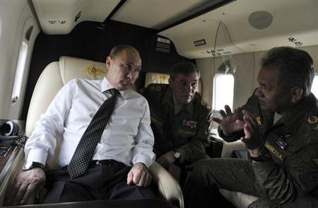 Russian President Vladimir Putin (L) speaks with Defence Minister Sergei Shoigu (R) and Chief of Staff Valery Gerasimov during a flight to watch military exercises in Russia's Zabaykalsky region July 17, 2013 file photo.REUTERS/Aleksey Nikolskyi