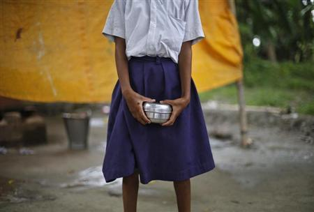 A school girl holds a container to receive her free mid-day meal, distributed by a government-run primary school, at Brahimpur village in Chapra district of Bihar July 19, 2013. REUTERS/Adnan Abidi