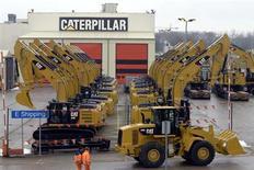 Рабочие проходят мимо техники Caterpillar в Госли 28 февраля 2013 года. Caterpillar Inc снизила прибыль во втором квартале 2013 год и сократила годовой прогноз, сообщив, что независимые дилеры компании сейчас озабочены сокращением запасов техники на складах. REUTERS/Eric Vidal