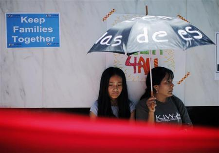 Diana Mendez (R), 39 and Ana Hernandez, 11, shelter from the sun at a 24-hour vigil calling on Congress to pass immigration reform in Los Angeles June 27, 2013. REUTERS/Lucy Nicholson