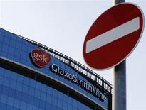 Дорожный знак на фоне здания GlaxoSmithKline в Хаунслоу, западный Лондон 18 июня 2013 года. Британская фармацевтическая компания GlaxoSmithKline, обвиненная в коррупции в Китае, сообщила о скромном двухпроцентном росте продаж и отметила, что скандал неизбежно скажется на ее результатах. REUTERS/Luke MacGregor