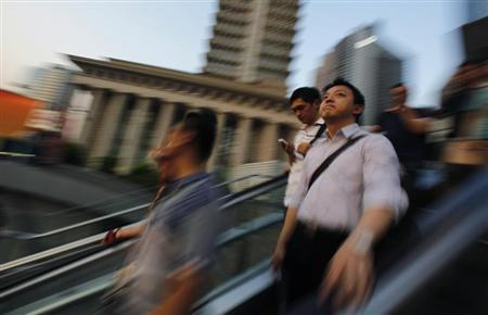 People take a escalator at the financial district of Pudong in Shanghai July 23, 2013. REUTERS/Carlos Barria