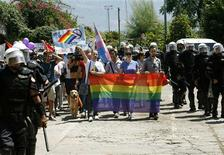 Riot police protect LGBT activists during a gay pride parade in Budva July 24, 2013. REUTERS/Stevo Vasiljevic