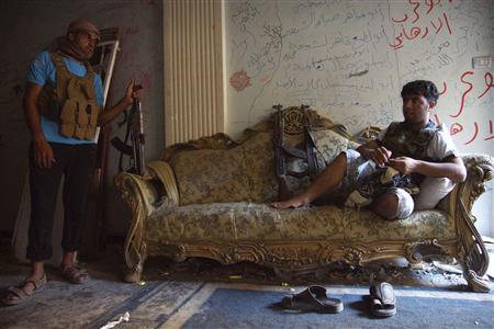 A Free Syrian Army fighter rests on a sofa as a fellow fighter stands near him inside a house in Deir al-Zor July 23, 2013. Picture taken July 23, 2013. REUTERS/Khalil Ashawi