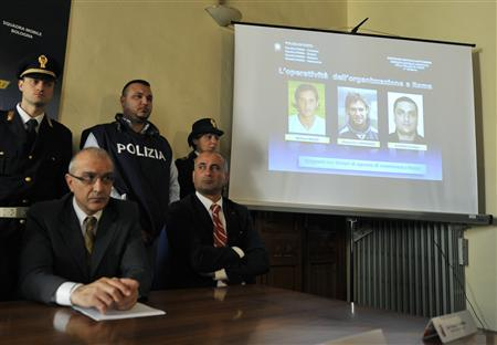 A presentation shows pictures of the two arrested players Stefano Mauri (L) and Alessandro Zamperini (C) of Italy and a Bosnian man Hristijan Ilievski, during a news conference about a police operation which was part of ''Last Bet'', a wider investigation into match-fixing in Italian soccer, in Cremona May 28, 2012. REUTERS/Paolo Bona