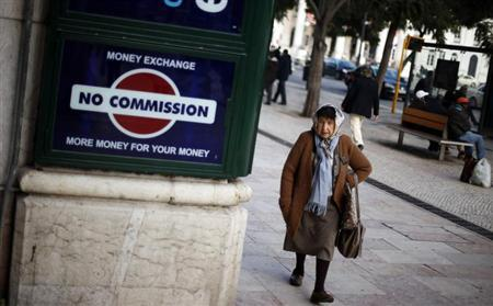 A woman walks past an exchange office in downtown Lisbon January 23, 2013. REUTERS/Rafael Marchante