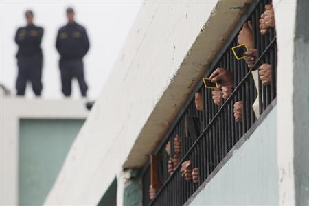 Inmates use mirrors to watch other inmates participate in a full-body resistance workout competition at the main courtyard, from their cell at Lurigancho prison in Lima, June 14, 2013. REUTERS/Enrique Castro-Mendivil