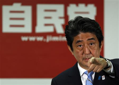 Japan's Prime Minister and the leader of the ruling Liberal Democratic Party (LDP), Shinzo Abe points to a reporter during a news conference following a victory in the upper house elections by his ruling coalition, at the LDP headquarters in Tokyo July 22, 2013. REUTERS/Issei Kato